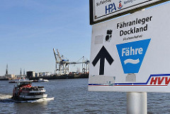 Schild Fähranleger Dockland - Hafenfähre, Elbfähre - vollbesetztes Fährschiff.