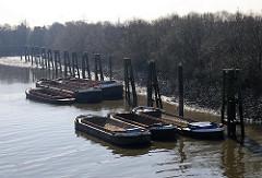 Leere Schuten / Lastkähne, Arbeitsschiffe an Dalben in Hamburg Wilhelmsburg, Klütjenfelder Hafen.