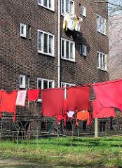 Wäsche zum Trocken in einem Innenhof in der Hamburger Jarrestadt. Wäsche hängt auf der Leine in der Sonne und auf einem Wäscheständer vor einem Fenste im 2. Stock.