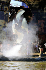 Werftarbeiten bei Blohm + Voss - Heck eines Frachtschiffs, das im Trockendock liegt - grosse Schiffsschraube; ein Hafenarbeiter arbeite mit einem Hochdruckwasserstrahl.