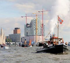Historische Schiffsparade im Hamburger Hafen - Dampfschlepper Claus D; Baustelle der Elbphilharmonie in der Hamburger Hafencity.