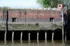 Alte Kaimauer im Hamburger Hafen; eingelassene Eisenringe zum Vertäuen von Schiffen. Bei Niedrigwasser zeigen sich die Baumstämme, die das Fundament der Kaianlage bilden.