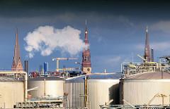 Erdöltanks auf dem Kleinen Grasbrook im Hamburger Hafen - im Hintergrund Kirchtürme der St. Petrikirche, St. Katharinenkirche und der St. Jacobikirche - weisser Rauch steigt aus einem Schornstein.