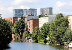 Wohnhäuser am Mittelkanal direkt am Wasser in Hamburg Hamm- Bäume und Sportboot - im Hintergrund Bürohochhäuser am Berliner Tor.