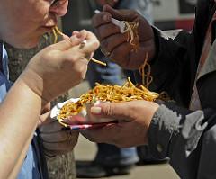 Fressmeile auf der Osterstrasse. Die Besucher und Besucherinnen essen im Stehen ein chinesiches Nudelgericht.