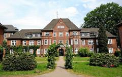 Hauptgebäude und Garten des Lankenaustift - Klinkerbau mit Pfannendach und Sprossenfenster - Denkmalschutz in Hamburg Altona, Ottensen.