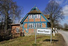 Stadtteilschild am Strassenrand - reetgedecktes Fachwerkhaus mit blauen Balken.