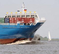 Containerfeeder in Fahrt auf der Elbe bei Hamburg - ein Segelschiff kreuzt in der Sonne auf der Elbe.