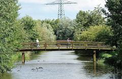 Baumbestand an einem der Fleete in Hamburg Neuallermöhe - eine Holzbrücke führt über das Wasser.