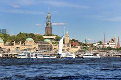 Blick über das Wasser der Elbe zu den St. Pauli Landungsbrücken - Fahrgastschiffe / Hafenrundfahrt liegen am Ponton, ein Segelschiff kreuzt auf der Elbe; im Hintergrund Kirchtürme der Hansestadt - St. Michaeliskirche; Michel in der Bildmitte.