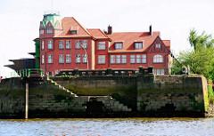 Alte Kaimauer mit Wassertreppe im Hamburger Hansahafen - Steinbalustrade und historisches Hafengebäude.