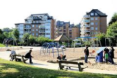 Spielplatz mit Spielgeräten auf dem Gelände des ehem. Freibad Lattenkamp - im Hintegrund Neubauten am Ufer des Alsterkanals in Hamburg Eppendorf.