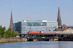Blick vom Oberhafenkanal zur Oberhafenbrücke - ein Zug mit roter Lokomotive überquert die Brücke über den Kanal - im Hintergrund das Deichtorcenter und die Kirchtürme der St. Petri und St. Jacobikirche.
