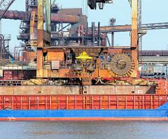 Die Ladung eines Frachtschiffs wird am Amsterdamer Kai des Dradenauhafens in Hamburger Waltershof entladen.