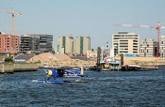 Blick in den Grasbrookhafen - im ein Wasserflugzeug nimmt auf der Elbe fahrt auf. Im Hintergrund neue und alte Gebäude beim Sandtorhafen. 2005
