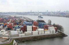 Blick auf ein Containerlager in Hamburg Waltershof; im Vordergrund die Einfahrt zur Rugenberger Schleuse - ein Containterfeeder läuft in den Hamburger Hafen ein und fährt auf der Süderelbe / Köhlbrand Richtung Terminal Altenwerder.