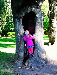 Ausgehöhlter Lindenstamm in der Lindenallee im Hirschpark in Hamburg Nienstedten - ein Kind blickt in den hohlen Baumstamm.