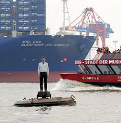 """Skulptur """"Mann auf Boje"""" Elbe, Hamburger Hafen - Künstler Stephan Balkenhol - im Hintergrund der Containerfrachter CMA CGM ALEXANDER VON HUMBOLDT und der Bug der Hafenfähre ELBMEILE."""