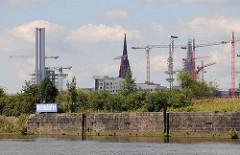 Alte Kaimauer im Moldauhafen - Namensschild den historischen Hafenbeckens - im Hintergrund Kräne der Baustelle Hafencity.