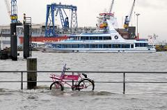 Die Elbe steigt über die Hafenmauer und überschwemmt das umliegende Gelände; ein am Geländer angeschlossenes Fahrrad steht im tiefen Wasser - im Hintergrund ein Schiff der Hafenrundfahrt mit Touristen, die das steigende Hochwasser beobachten.