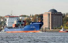 Der Containerfrachter WES Janine auf der Elbe vor Hamburg Ottensen - am Elbufer das zu einer Seniorenresidenz umgebaute ehem. Kühlhaus von Hamburg Neumühlen.