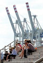 Mittagspause am Hafen - Angestellte der umliegenden Bürohäuser geniessen die Sonne an der Grossen Elbstrasse in Hamburg Altona; im Hintergrund hochgefahrene Containerkräne des HHLA Terminals Tollerort.