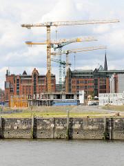 Kaimauer am Versmannkai - Baukräne am Magdeburger Hafen in der Hafencity Hamburg - im Hintergrund der Kaispeicher B - das Maritime Museum Hamburg.