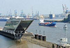 Bürogebäude Dockland am Altonaer Elbufer; ein Containerfeeder läuft aus dem Hamburger Hafen aus.