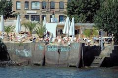 Beachclub an der Großen Elbstraße  - Menschen in Liegestühlen in der Sonne an der Elbe - Inschrift an der Kaimauer Viva Bambule (2005)
