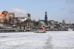 Eis auf der Elbe - eisbedecktes Wasser vor den Hamburger Landungsbrücken - Hafenfähre vor den St. Pauli Landungsbrücken.