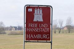 Schild Freie und Hansestadt Hamburg, weisses Hamburger Wappen auf rotem Grund.