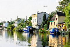 Häuser am Bullenhusener Kanal in Hamburg Rothenburgsort - an den Bootsstegen haben Motorboote festgemacht.