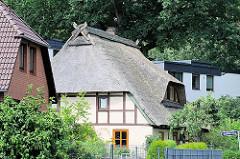 Reetdachgebäude mit Fachwerkmauern zwischen neuerrichteten Einzelhäusern im Hamburger Stadtteil Eißendorf.