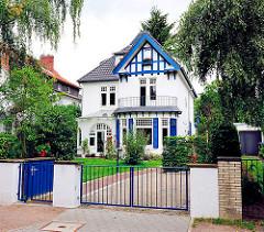 Einzelhaus in einer Seitenstrasse in Hamburg Lokstedt - blau gestrichene Fensterläden und Fachwerkbalken.
