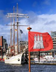 Fahne von Hamburg  - Flagge der Hansestadt an der Elbe. Segelschiff im Hintergrund.