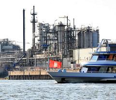 Industrieanlage am Ufer der Norderelbe in Hamburg Steinwerder - ein Schiff der Hafenrundfahrt fährt auf der Elbe.