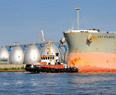 Das Frachtschiff / Bulk Carrier Lily Atlantic wird von dem Schlepper Bugsier 18 im Köhlbrand / Süderelbe geschleppt - im Hintergrund die Faultürme des Hamburger Klärwerks Köhlbrand.