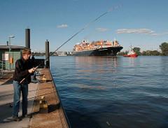 Angler auf dem Waltershofer Anleger - ein Containerschiff wird von Schleppern zum Terminal Altenwerder geschleppt.