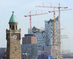 Uhr und Pegelturm der St. Pauli Landungsbrücken; Baukräne und Bauvorhaben der Elbphilharmonie mit entstehender moderner Glasfassade.