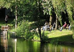 Hamburg-Bilder / Fotos aus den Stadtteilen - Erholung im Eimsbüttler Park Am Weiher - Menschen sitzen auf Parkbänken in der Sonne am Wasser.