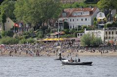 Strandleben in Hamburg Othmarschen - Sonne in Hamburg am Elbufer - Festmacherboot und Skulptur vier Männer auf Bojen.