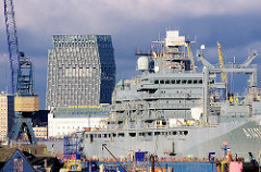 """Blick über den Reiherstieg - der Einsatzgruppenversorger A 1411 liegt eingedockt in der Werft - im Hintergrund das Hotel Hafen Hamburg und das Hochhaus """"Tanzende Türme"""" an der Hamburger Reeperbahn."""