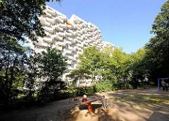 Hochhaus der Siedlung Osdorfer Born in Hamburg Osdorf - Kinderspielplatz unter Bäumen.