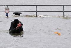 Hochwasser in Hamburg - Sturmflutwarnung im Hafen; ein Fotograf nutzt das Hochwasser um Aufnahmen zu machen.