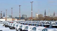 Für den Weitertransport abgestellte Neufahrzeuge - O'swaldkai Terminal; gegen Transportschäden sind die neuen Kraftfahrzeuge abgedeckt. Im Hintergrund auf der anderen Elbseite die Türme der Hansestat Hamburg