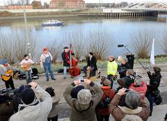 Musiker am Ufer des Spreehafen spielen auf der Veranstaltung zum Abriss des Zollzauns. Zuschauer fotografieren die Veranstaltung vom Deich - im Hintergrund ein Polizeiboot der Hamburger Wasserschutzpolizei im Spreehafen.