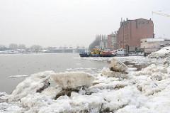Eisschollen in der Billwerder Bucht von Hamburg Rothenburgsort - historische Industriearchitektur am Ufer. Im Hintergrund das Billwerder Sperrwerk - Hochwasserschutz in Hamburg.