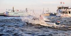 Ein kleines Sportboot  im Wellengang des Hamburger Hafens - Gischt spritzt hoch auf; im Hintergrund zwei Fahrgastschiffe bei einer Hafenrundfahrt.
