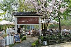 Gartencafé Altes Fährhaus - Tische unter blühenden Krischbäumen.