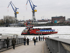 Eine Hafenfähre legt von den St. Pauli Landungsbrücken ab und fährt durch die Eisschollen auf der Elbe Richtung Hamburg Altona.